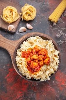 Pollo di vista superiore con il piatto di pasta della pasta su una pasta scura del piatto della pasta di superficie scura