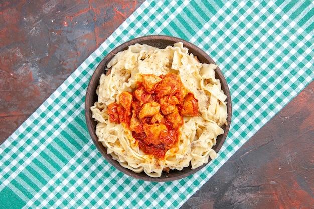 Pollo di vista superiore con il piatto di pasta della pasta sul colore del piatto di pasta del pasto di superficie scura