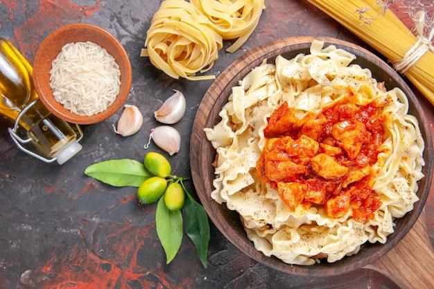 Pollo di vista superiore con il piatto di pasta della pasta sulla pasta del piatto di pasta di superficie scura