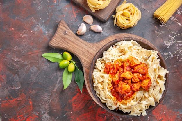 Pollo di vista superiore con piatto di pasta della pasta sul piatto della pasta della pasta di superficie scura scuro