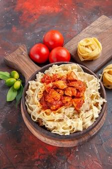 Pollo di vista dall'alto con piatto di pasta di pasta con pomodori sulla farina di pasta di pasta scura scrivania