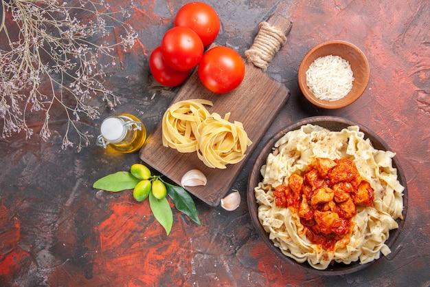 Pollo di vista superiore con piatto di pasta della pasta con i pomodori sulla farina della pasta della pasta del pavimento scuro