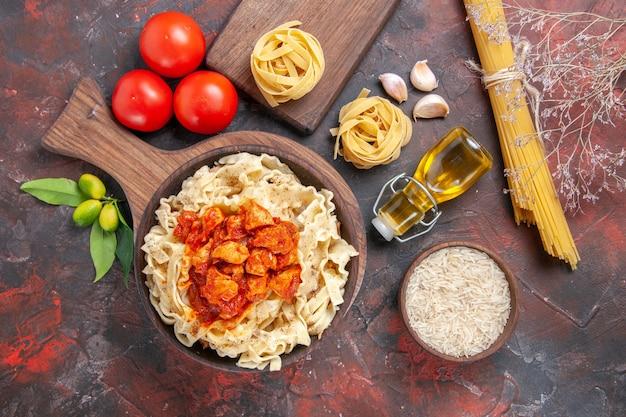 Vista dall'alto di pollo con pasta piatto di pasta con pomodori su pasta di superficie scura