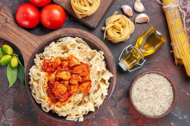 暗い床のパスタ生地の食事にトマトと生地のパスタ料理とトップビューチキン