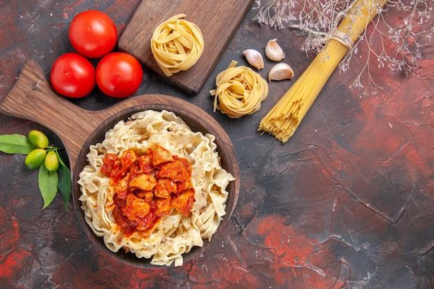 暗い表面のパスタ生地の食事にトマトと生地のパスタ料理とトップビューチキン