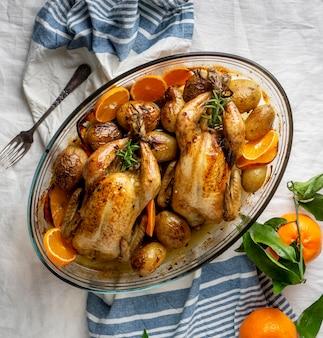 Вид сверху курица с картофелем и апельсином