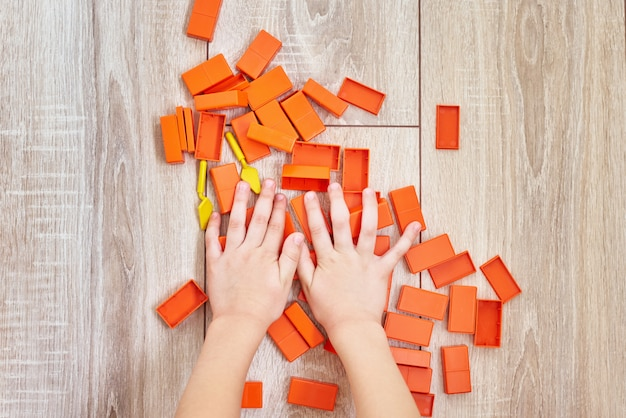 Top view of child hands playing with orange toy bricks. concept of kids lerning and education. baby leisure with developing toys