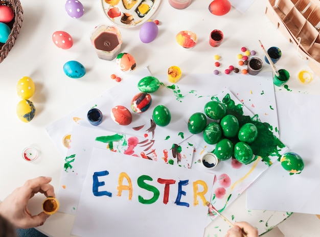Top view child painting traditional easter eggs