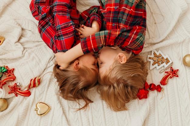Вид сверху на детей, лежащих в постели на рождество