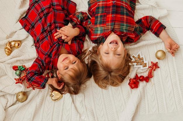 Вид сверху дети веселятся в постели на рождество
