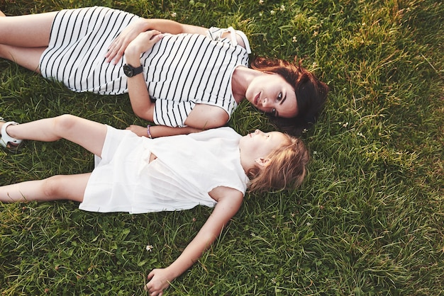 Top view of children and mother laying down on the grass filled with sunshine and looking at each other