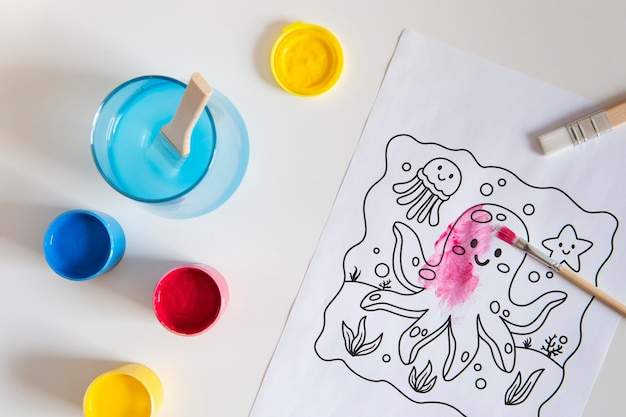 Top view of children's desk with paint and drawing