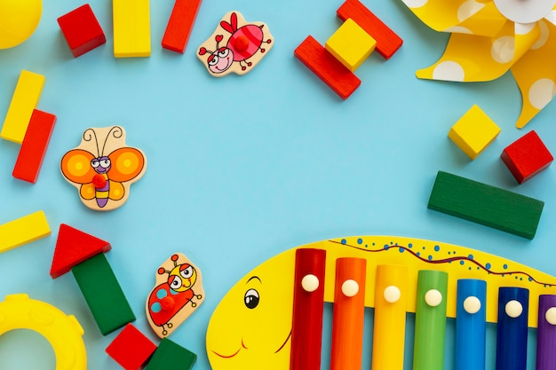 Top view on children's educational games, frame from multicolored kids wooden toys on light blue paper background. flat lay, copy space for text.