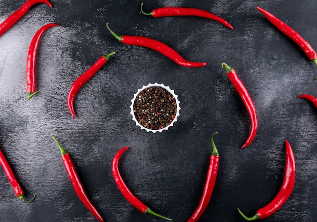 Top view chili pepper pattern with spices in middle on black stone  horizontal
