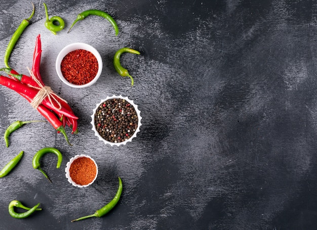 Top view chili pepper with spices in white bowls on black stone  horizontal