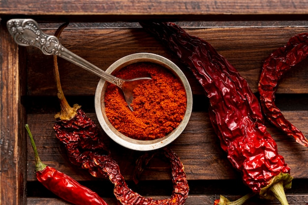 Top view of chili peppers on wooden tray with powder