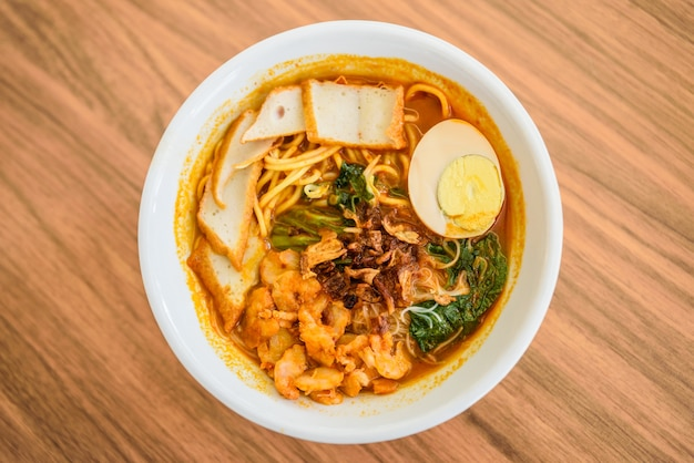 Top view of chinese chopsticks eating noodle, a famous malaysia prawn noodle curry soup.