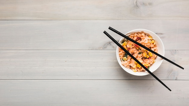 Top view of chinese fried rice bowl with black chopsticks on wooden table