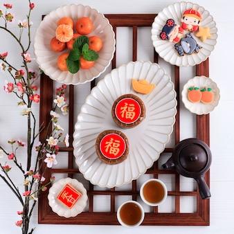 Вид сверху китайский новогодний торт (китайский иероглиф «фу» означает удачу). популярный как куэ керанжанг или додол китай в индонезии. подается с печеньем и украшением из красного апельсина имлек