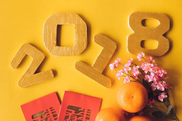 Top view of chinese new year festival decorations with numbers 2018 on yellow background.