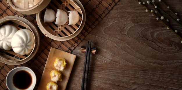 Top view of chinese steamed dumpling and steamed pork bun in a bamboo steamer with chopstick on wooden table