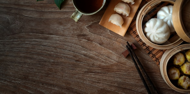 Top view of chinese steamed dumpling and steamed pork bun in a bamboo steamer