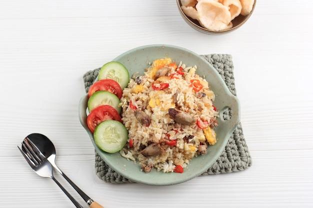 Top view жареный рис по-китайски с соленой рыбой из кальмаров (nasi goreng cumi asin). подается на тарелке зеленая тоска с крупук уданг (креветочный крекер). копировать пространство для текста на белом фоне