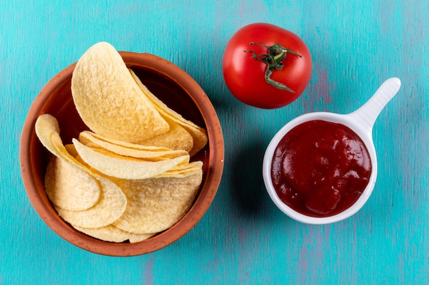 Top view chips in bowl with tomato and sause on blue  horizontal