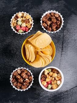 Vista dall'alto di patatine e popcorn in ciotole su verticale nero