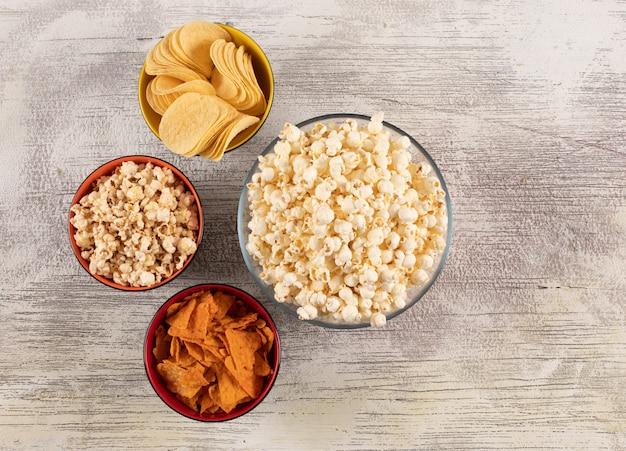 Vista superiore delle patatine fritte e del popcorn in ciotole sull'orizzontale di legno bianco