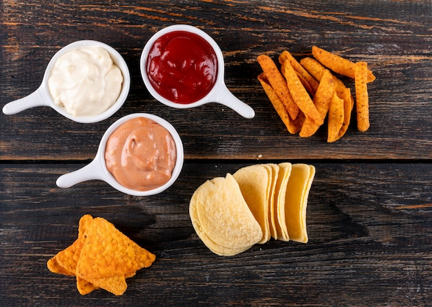 Top view chips with sauses in bowls on brown wooden