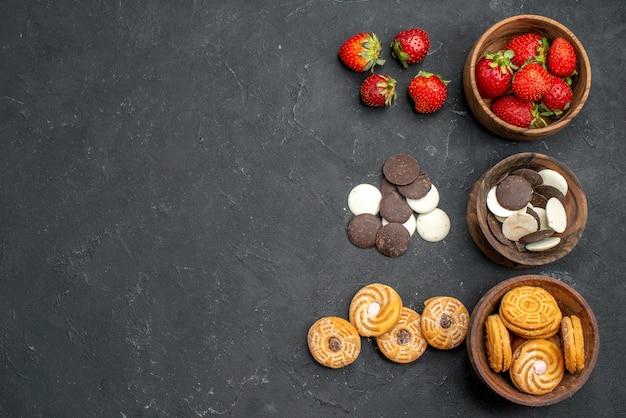 Вид сверху шоколадное печенье с клубникой и печеньем на темной поверхности