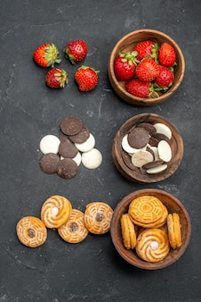 Top view choco cookies with strawberries and biscuits on dark desk