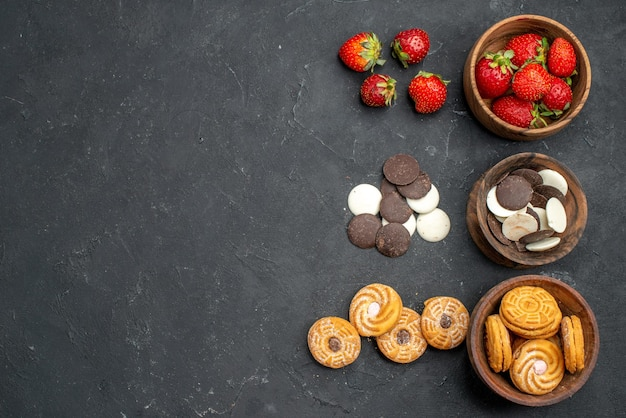 Top view choco cookies with strawberries and biscuits on dark surface