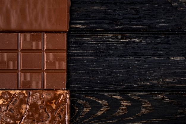 Top view of chocolate bar on dark rustic background with copy space