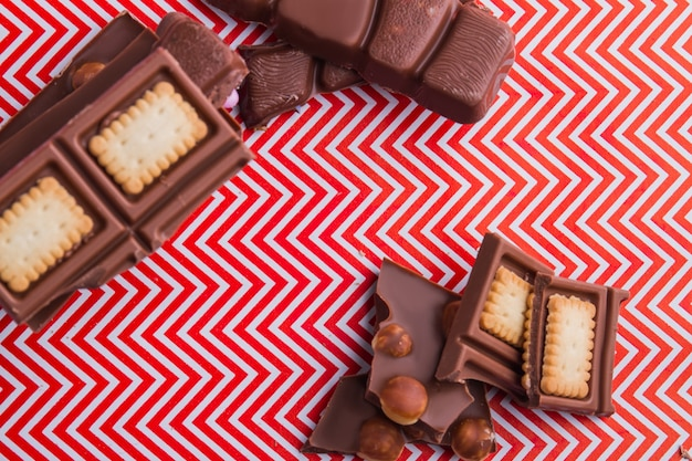 Кусочки плитки шоколада вида сверху с коренастым печеньем и фундуком. плоский вид сверху.
