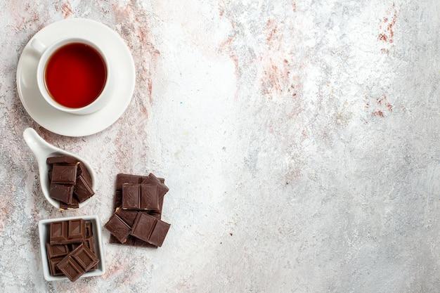 Vista dall'alto di barrette di cioccolato con una tazza di tè sulla superficie bianca