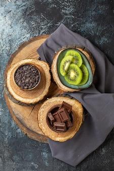 ダークグレーの表面のケーキの色の朝食シュガーフルーツデザートに新鮮なスライスされたキウイとトップビューチョコレートバー