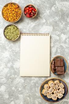 白いテーブルの色のフルーツベリーシードにフルーツとトップビューチョコレートバー