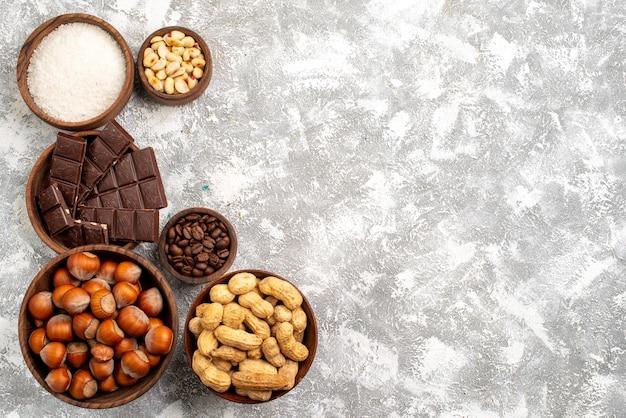 Vista dall'alto di barrette di cioccolato con nocciole e arachidi sulla superficie bianca