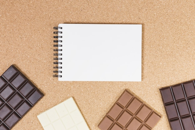 Top view chocolate bars with notebook