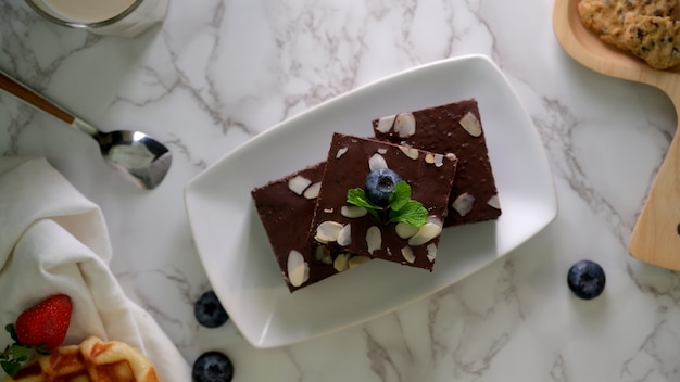 Top view of chocolate brownies on white plate with and blueberries decorated on marble table