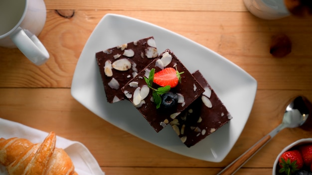 Top view of chocolate brownies on white plate with mint leaf on top