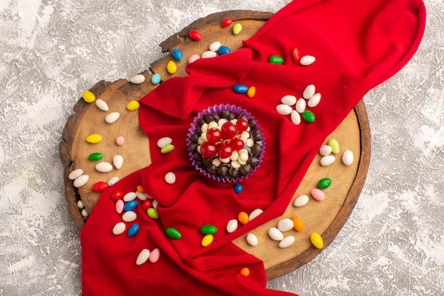明るい背景のケーキビスケット焼きにクランベリーとキャンディーの平面図チョコレートブラウニー