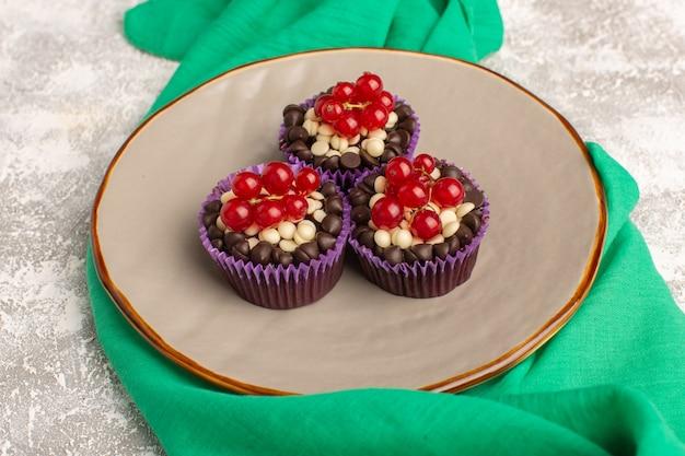 Вид сверху шоколадные пирожные с клюквой внутри тарелки светлый стол с зеленой салфеткой, печенье, бисквит, сладкое тесто для выпечки