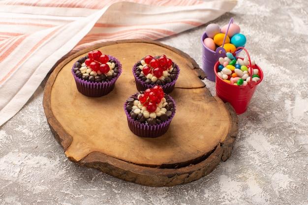 Вид сверху шоколадные пирожные с клюквой на деревянном столе с конфетами, торт, бисквит, сладкое тесто для выпечки