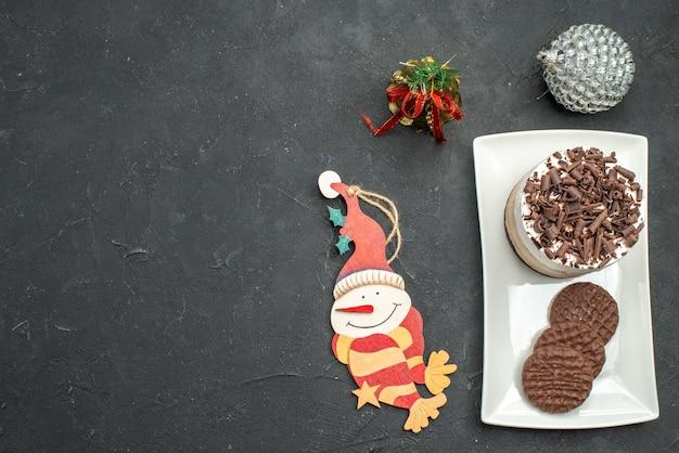 暗い孤立した背景の上の白い長方形のプレートのクリスマスツリーのおもちゃの上面図チョコレートケーキとビスケット