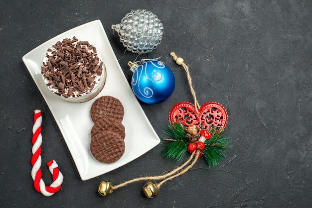 Вид сверху шоколадный торт и печенье на белой прямоугольной тарелке елочные игрушки на темном изолированном фоне