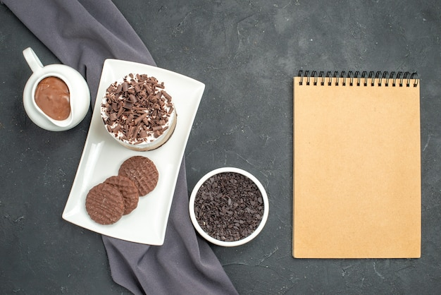 Top view chocolate cake and biscuits on white rectangular plate bowls with chocolate on dark isolated background