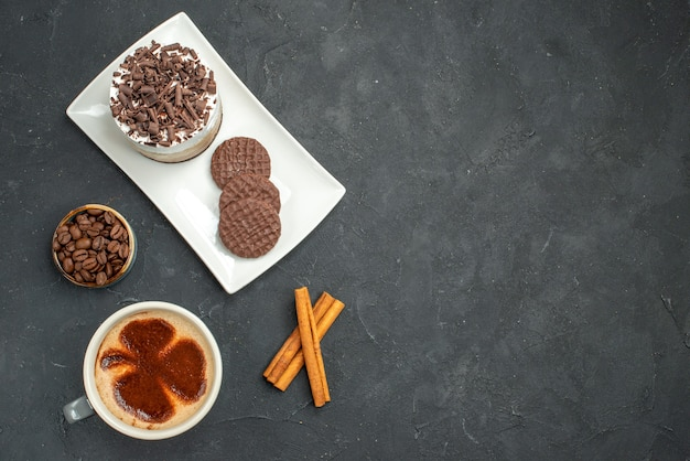 Top view chocolate cake and biscuits on white rectangular plate cup of coffee cinnamon sticks bowl with coffee seeds on dark isolated background